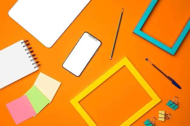 Concetto di scrivania piatto laici con sfondo arancione