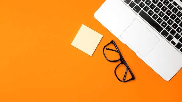 Concetto di scrivania vista dall'alto con sfondo arancione