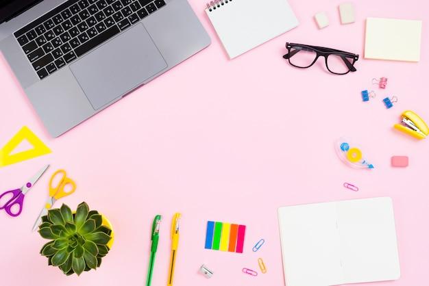 Concetto di scrivania vista dall'alto con sfondo rosa