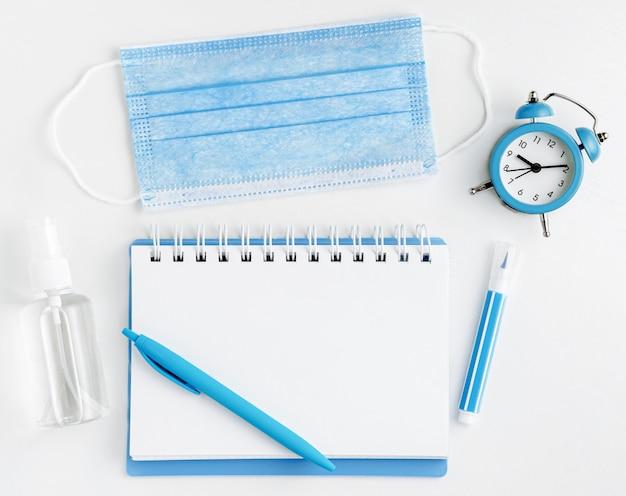 Concetto di scuola a casa. bottiglia in bianco, maschera e disinfettante del taccuino su bianco. vista dall'alto