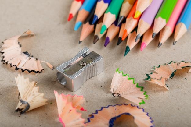 Concetto di scuola e attrezzature con matite, temperamatite, trucioli su carta alta.