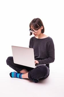 Concetto di scuola, istruzione, internet e tecnologia - giovane ragazza adolescente seduta sul pavimento con il computer portatile
