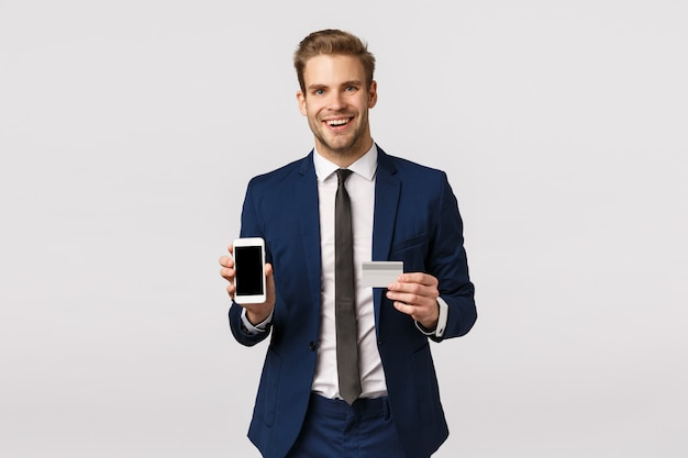 Concetto di servizi bancari, finanziari e commerciali online. il riuscito uomo d'affari caucasico bello in vestito classico, promuove il sistema bancario, mostrando l'esposizione dello smartphone e la carta di credito, sorridenti