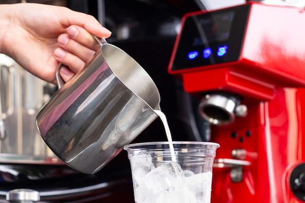Concetto di servizio di preparazione della preparazione del caffè di ghiaccio. il barista fa il caffè espresso in un caffè versando il latte