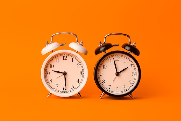 Concetto di sfondo del tempo. sveglia classica d'annata su fondo vuoto arancio. comcept di gestione del tempo