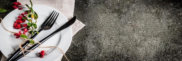 Concetto di sfondo di cibo autunnale. cena del ringraziamento, tavolo in pietra scura con set di coltelli per posate, forchetta con bacche autunnali come decorazione. sfondo nero. copia banner spaziale