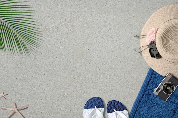 Concetto di sfondo estivo, cappello di paglia, asciugamano, macchina fotografica, pantofole, deve e foglia verde sulla sabbia