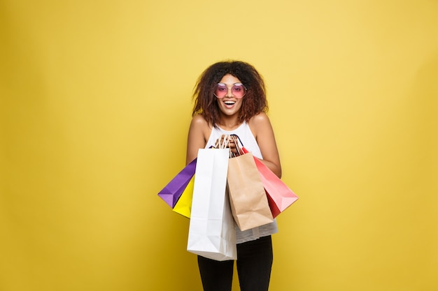 Concetto di shopping - close up ritratto di giovane bella donna attraente africana sorridente e gioiosa con shopping bag colorato. giallo pastello sfondo muro. copia spazio.