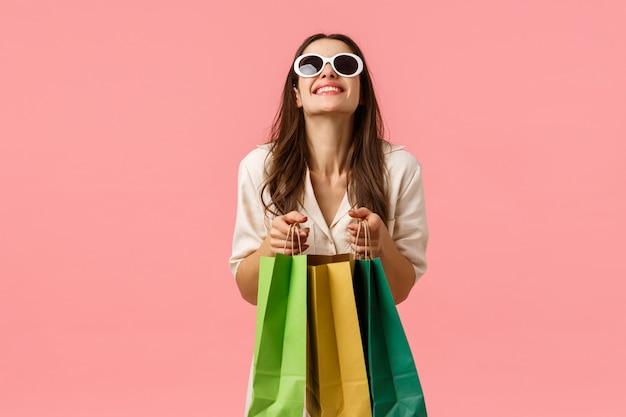 Concetto di shopping, moda e bellezza. ragazza felice ed eccitata che compra nuovi vestiti per le vacanze estive, facendo i bagagli, tenendo i sacchetti della spesa, ridendo in piedi parete rosa entusiasta