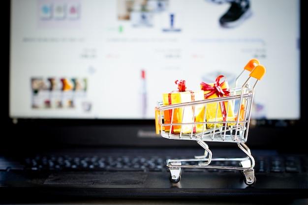 Concetto di shopping online, carrello, piccole scatole, computer portatile sulla scrivania