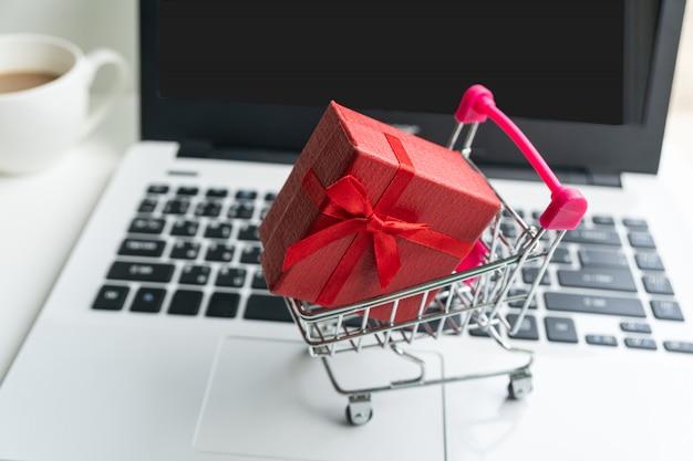 Concetto di shopping online. carrello, scatola piccola, laptop, sulla scrivania, copia spazio, da vicino