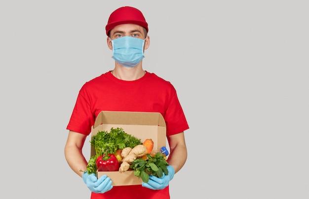 Concetto di shopping online. il corriere maschio in uniforme rossa, maschera protettiva e guanti con un contenitore di drogheria frutta e verdura fresca detiene un banner bianco per il testo. consegna a domicilio di alimenti durante la quarantena
