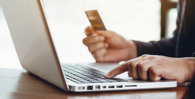 Concetto di shopping online. mani in possesso di carta di credito per lo shopping online a casa