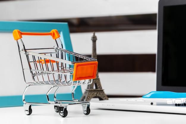 Concetto di shopping online. piccolo carrello giocattolo e gadget sul tavolo