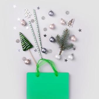 Concetto di shopping vacanze di natale. borsa verde con acquisti festivi, decorazioni, coriandoli glitter su sfondo grigio.