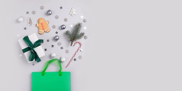 Concetto di shopping vacanze di natale. borsa verde con regali festivi, bastoncino di zucchero, dolcetti, decorazioni, coriandoli glitter su sfondo grigio.