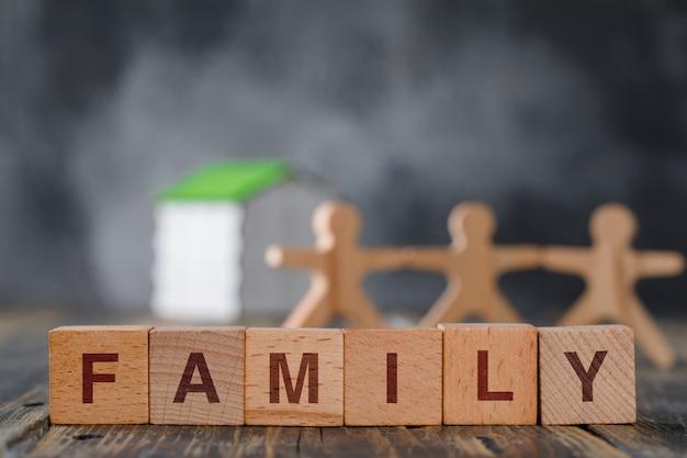 Concetto di sicurezza familiare con figure in legno di persone, cubi, vista laterale della casa modello.