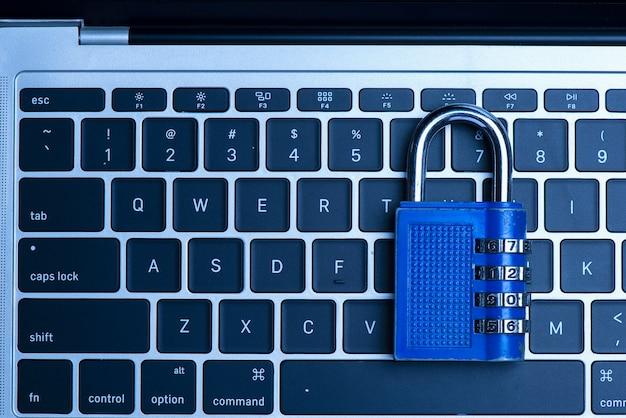 Concetto di sicurezza informatica con un lucchetto blu chiuso sopra la tastiera