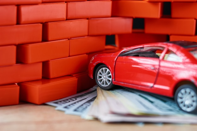 Concetto di sicurezza stradale. automobile rotta e banconote da un dollaro.