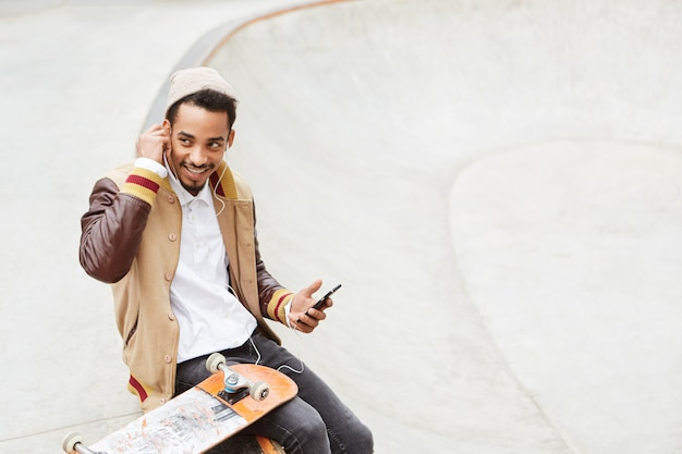Concetto di skateboard. elegante adolescente spensierato fa skateboard, si riposa dopo una giornata attiva,