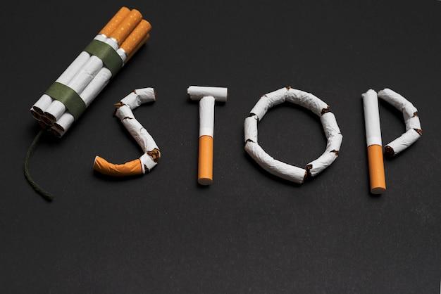 Concetto di smettere di fumare con un mucchio di sigarette su sfondo nero