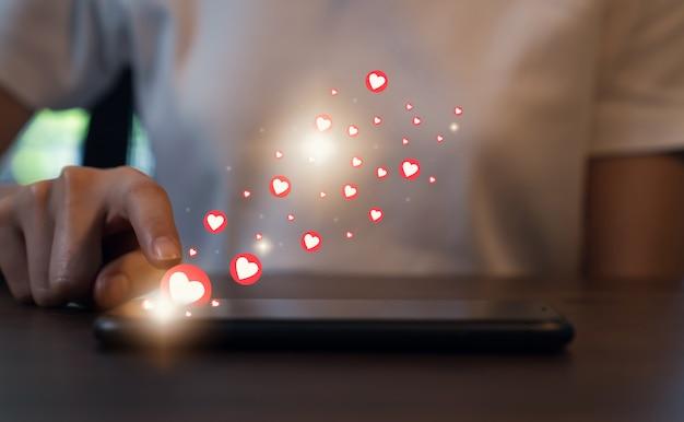 Concetto di social network. telefono della stampa della mano della donna e icona del cuore di manifestazione.