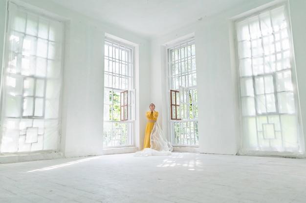 Concetto di solitudine. una donna in un abito giallo è in piedi in un angolo