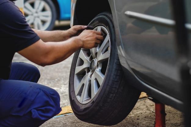 Concetto di sostituzione della gomma. meccanico che lavora il suo lavoro con wheel in garage. manutenzione e servizi dell'automobile