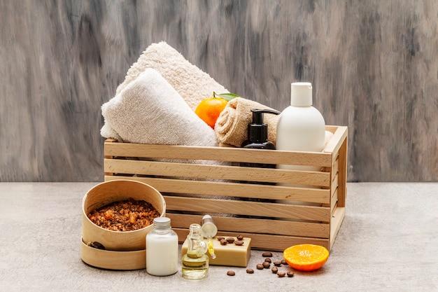 Concetto di spa di caffè e mandarino. asciugamani, olio, scrub, sapone, lozione. ingrediente naturale, scatola di legno.
