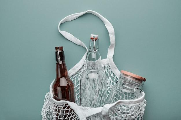 Concetto di spesa alimentare zero rifiuti. sacchetti di cotone, bottiglie di vetro e vaso.