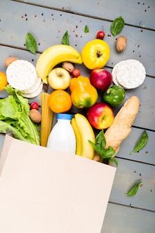 Concetto di spesa. alimento differente in sacco di carta su di legno. disteso.