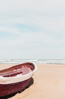 Concetto di spiaggia con barca rossa