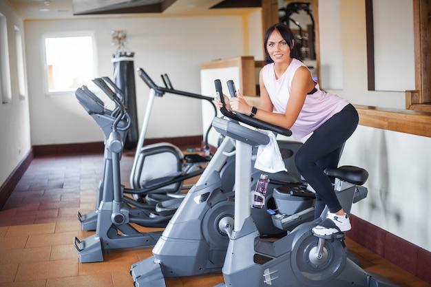 Concetto di sport e stile di vita sano. esercizio di gambe facendo allenamento cardio sulla bici da ciclismo
