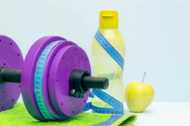 Concetto di sport e stile di vita sano. manubri allenamento, acqua, asciugamano, mela su sfondo blu.