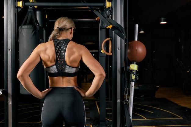 Concetto di sport, fitness, stile di vita e persone. donna che esercita e facendo pull-up in palestra dalla parte posteriore