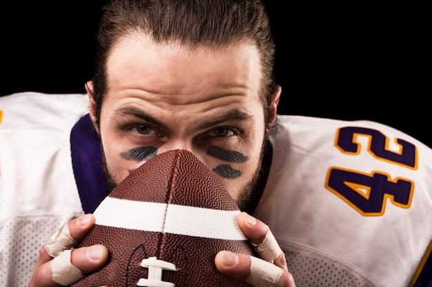 Concetto di sport. giocatore di football americano sul nero con la palla. concetto di sport. avvicinamento