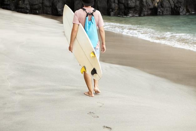 Concetto di sport, hobby e stile di vita sano. retrovisione di giovane uomo scalzo che cammina lungo la riva di mare