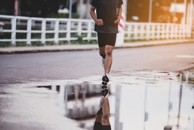 Concetto di sport, primo piano l'uomo con il corridore per strada