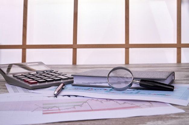 Concetto di statistiche aziendali con grafici statistici con lente di ingrandimento in vetro