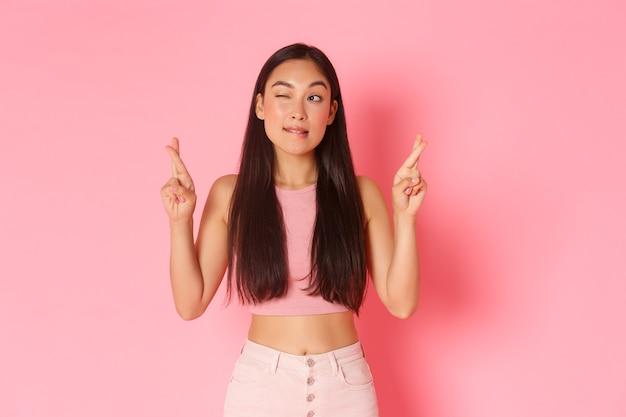 Concetto di stile di vita, bellezza e donne. ritratto di ragazza asiatica carina anticipando momento, dita incrociate buona fortuna, esprimendo desiderio e sbirciando nell'angolo in alto a sinistra al tabellone dei risultati, muro rosa.