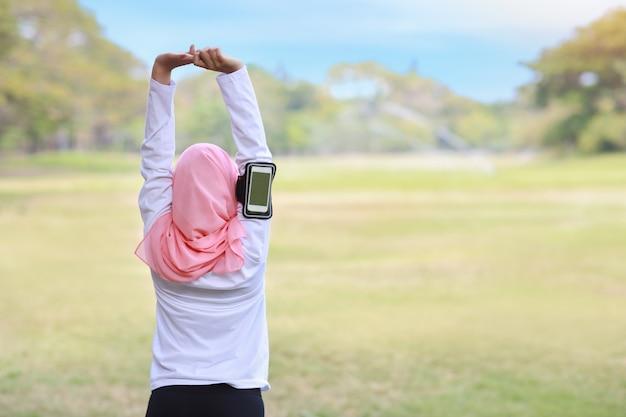 Concetto di stile di vita di esercizio pubblico, musica d'ascolto della donna di forma fisica dalle cuffie senza fili e telefono cellulare. giovane ragazza musulmana asiatica atletica di retrovisione nella condizione degli abiti sportivi, allungante dopo l'allenamento