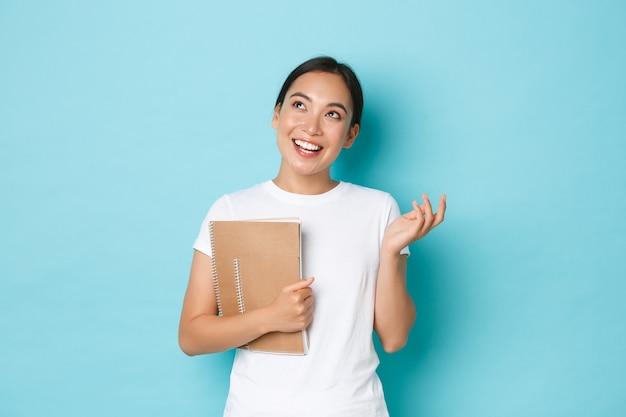 Concetto di stile di vita, educazione e persone. felice bella studentessa asiatica in maglietta bianca, ragazza che parla e che sembra sognante nell'angolo in alto a sinistra mentre si tiene i taccuini, parete blu chiaro