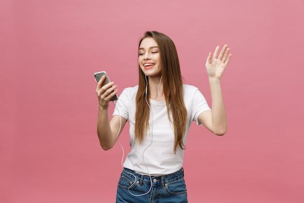 Concetto di stile di vita. giovane donna che per mezzo del telefono per l'ascolto di musica su sfondo rosa