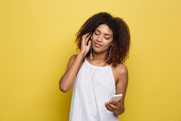 Concetto di stile di vita - ritratto di bella donna afroamericana allegra ascoltare musica sul cellulare. sfondo di studio pastello giallo. copia spazio.