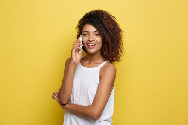 Concetto di stile di vita - ritratto di bella donna afroamericana allegra parlando sul cellulare con un amico. sfondo di studio pastello giallo. copia spazio.