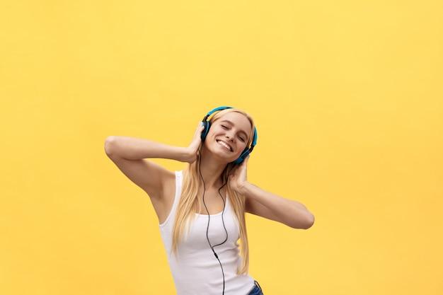 Concetto di stile di vita: ritratto di una donna gioiosa in t-shirt bianca e ascoltare musica
