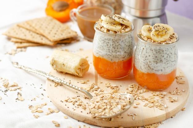 Concetto di stile di vita sano. colazione con caffè, cracker, fiocchi d'avena, budino di semi di chia con banana e albicocca