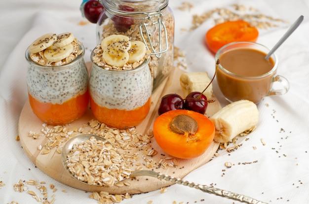 Concetto di stile di vita sano. colazione con caffè, farina d'avena, budino di semi di chia con frutta su tavola di legno.