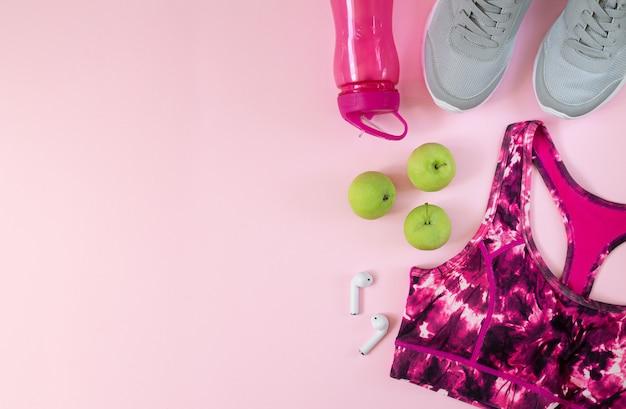 Concetto di stile di vita sano. reggiseno fitness, scarpe sportive, bottiglia, auricolari e mele verdi vista dall'alto con spazio per il testo