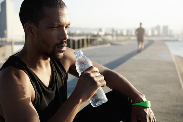 Concetto di stile di vita sano. ritratto di profilo di sportivo nero con corpo muscoloso seduto sul marciapiede nel sole del mattino dopo esercizi di allenamento, tenendo bottiglia, acqua potabile, guardando in lontananza